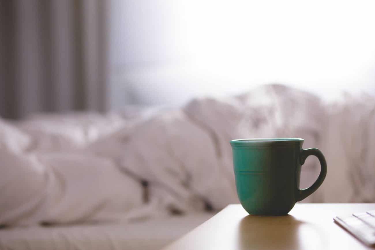Kaffeetasse auf Nachtisch vor einem Bett