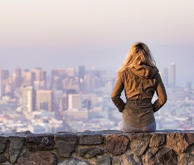 Blonde junge Dame Blick sitzend auf einer Steinmauer mit Blick auf eine städtische Skyline