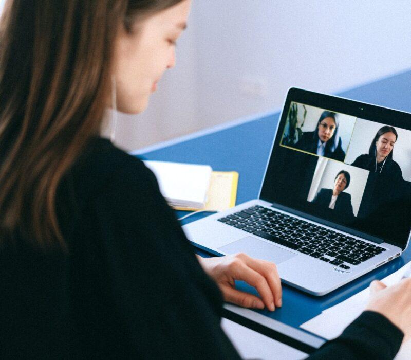 Eine Studentin sitzt vor ihrem Laptop und ist in einem Online-Meetingroom mit drei weiteren Personen